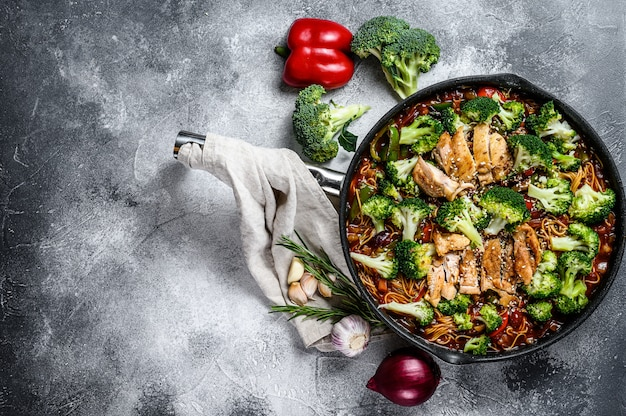 Asian egg noodles with vegetables and meat on cooking pan. top view. Premium Photo