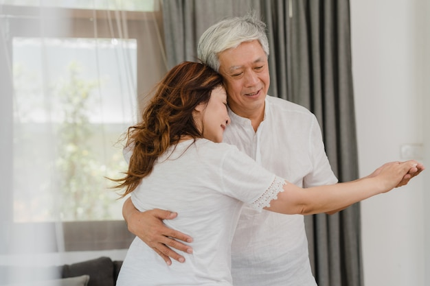 Asian elderly couple dancing together while listen to music in living room at home, sweet couple enjoy love moment while having fun when relaxed at home. lifestyle senior family relax at home concept. Free Photo
