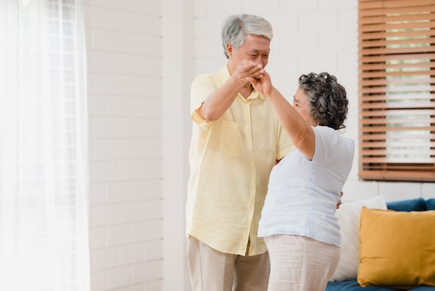 Asian elderly couple dancing together while listen to music in living room at home, sweet couple enjoy love moment while having fun when relaxed at home. Free Photo