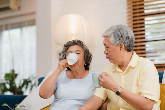 Asian elderly couple drinking warm coffee and talking together in living room at home, couple enjoy love moment while lying on sofa when relaxed at home Free Photo