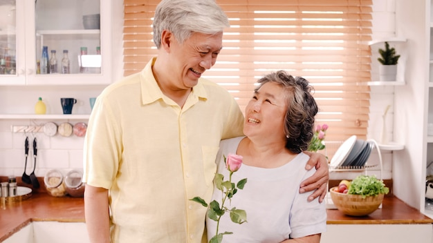Asian elderly couple feeling happy smiling and holding flower and looking to camera while relax in kitchen at home. lifestyle senior family enjoy time at home concept. portrait looking at camera. Free Photo