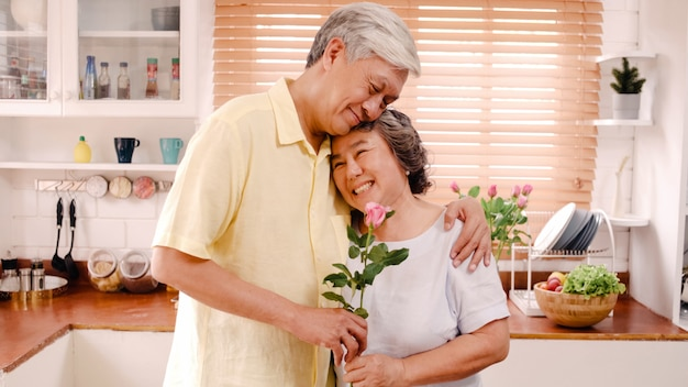 Asian elderly couple feeling happy smiling and holding flower and looking to camera while relax in kitchen at home. lifestyle senior family enjoy time at home concept. Free Photo