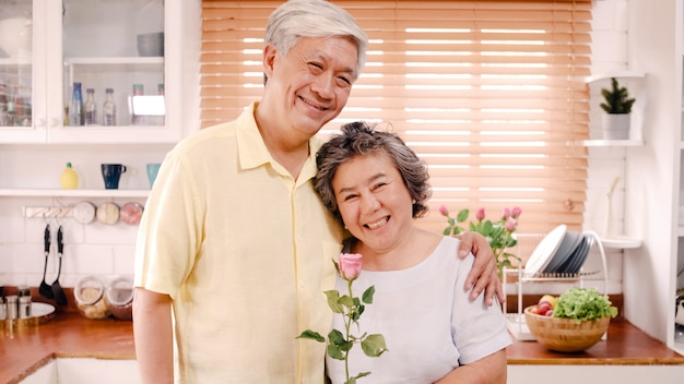 Asian elderly couple feeling happy smiling and holding flower and looking to camera while relax in kitchen at home. Free Photo