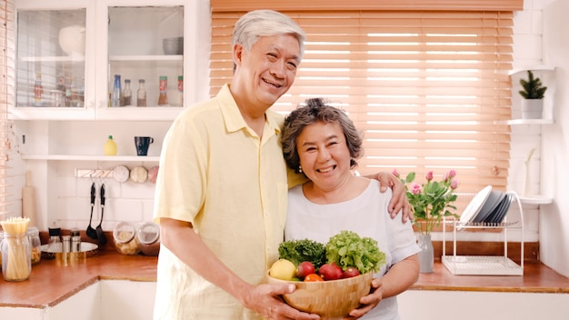 Asian elderly couple feeling happy smiling and holding fruit and looking to camera while relax in kitchen at home. lifestyle senior family enjoy time at home concept. Free Photo