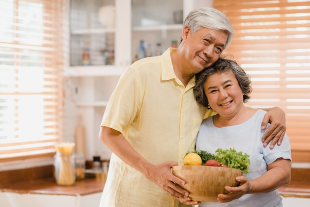 Asian elderly couple feeling happy smiling and holding fruit and looking to camera while relax in kitchen at home. Free Photo