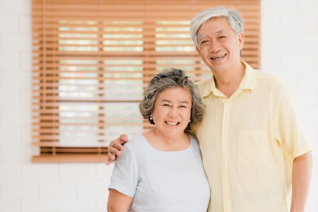 Asian elderly couple feeling happy smiling and looking to camera while relax in living room at home. Free Photo