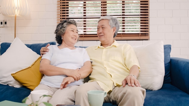 Asian elderly couple feeling happy smiling and looking to camera while relax on the sofa in living room at home. Free Photo