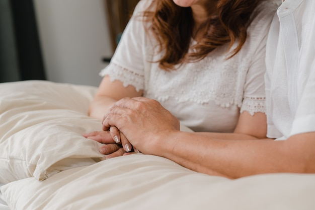 Asian elderly couple holding their hands while taking together in bedroom, couple feeling happy share and support each other lying on bed at home. lifestyle senior family at home concept. Free Photo