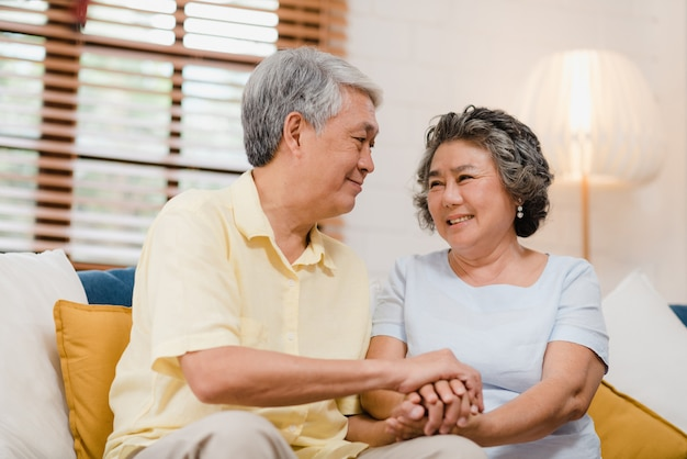 Asian elderly couple holding their hands while taking together in living room, couple feeling happy share and support each other lying on sofa at home. Free Photo