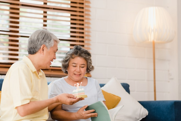 Asian elderly couple man holding cake celebrating wife's birthday in living room at home. japanese couple enjoy love moment together at home. Free Photo