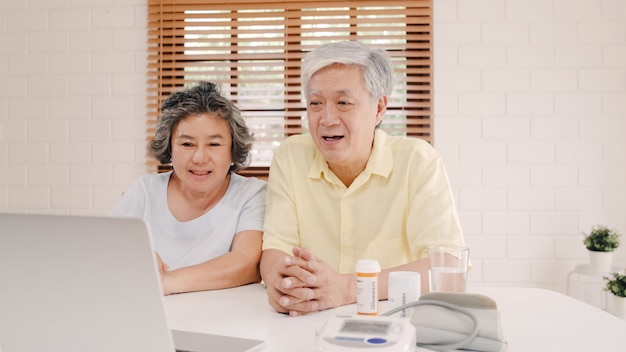 Asian elderly couple using laptop conference with doctor about medicine information in living room, couple using time together while lying on sofa at home. Free Photo