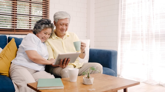 Asian elderly couple using tablet and drinking coffee in living room at home, couple enjoy love moment while lying on sofa when relaxed at home. Free Photo