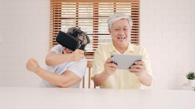 Asian elderly couple using tablet and virtual reality simulator playing games in living room, couple feeling happy using time together lying on table at home. Free Photo