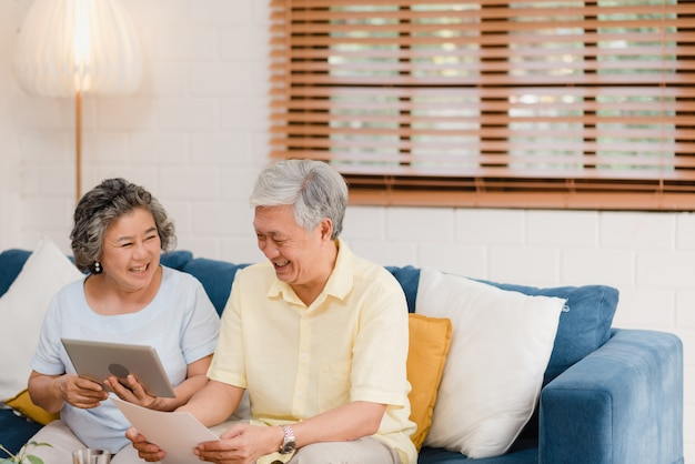 Asian elderly couple using tablet watching tv in living room at home, couple enjoy love moment while lying on sofa when relaxed at home. Free Photo
