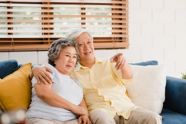 Asian elderly couple watching television in living room at home, sweet couple enjoy love moment while lying on the sofa when relaxed at home. Free Photo