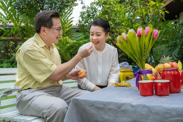 Asian elderly couples are taking care of each other by stripping oranges to eat. family concept, couples concept Premium Photo