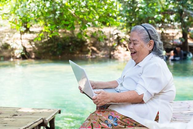 Asian elderly female enjoy with laptop Free Photo