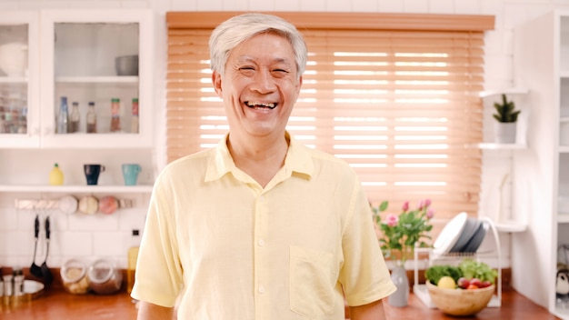 Asian elderly man feeling happy smiling and looking to camera while relax in kitchen at home. Free Photo