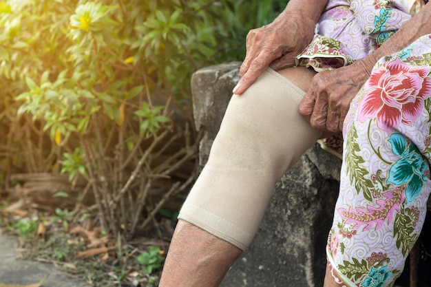 Asian elderly people or older woman wearing the knee support Premium Photo