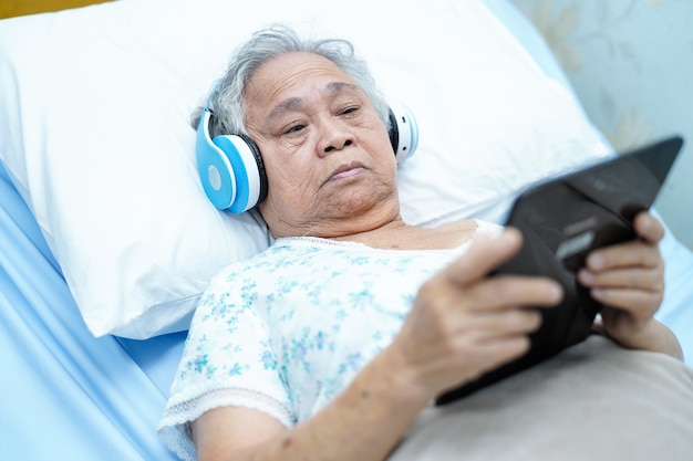 Asian elderly woman holding digital tablet on bed and listen to music while lie down. Premium Photo