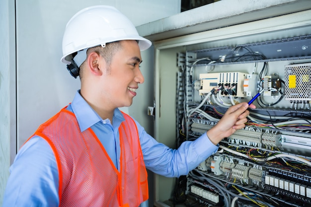Asian electrician at panel on construction site Premium Photo