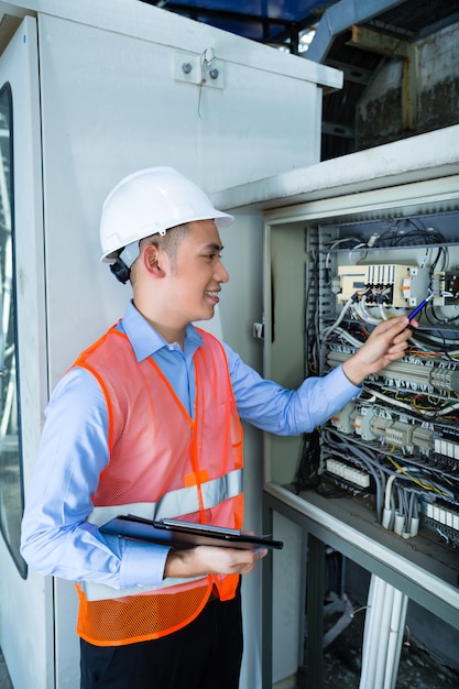 Asian electrician at panel on construction site | Premium ...