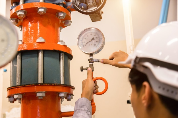 Asian engineer maintenance checking technical data of  system equipment condenser water pump and pressure gauge , chiller water pump with pressure gauge. Premium Photo