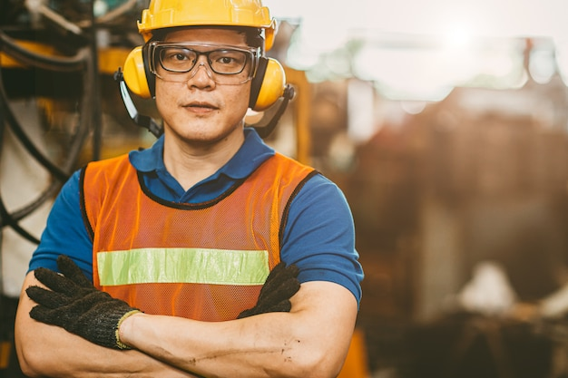 Asian engineer worker wearing earmuffs ears protection anti noise and safety suit working in factory portrait. Premium Photo