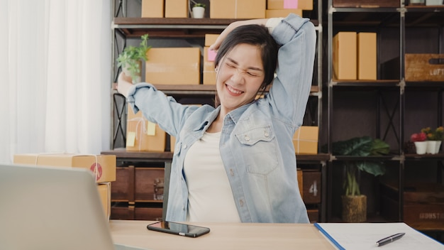 Asian entrepreneur business woman stretching her body after answer customer question Free Photo