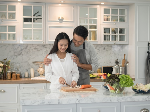 Asian expecting pregnant couple cooking together in the kitchen at home Premium Photo