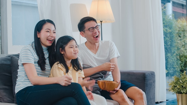 Asian family enjoy their free time relax together at home. lifestyle dad, mom and daughter watch tv together in living room in modern home at night . Free Photo