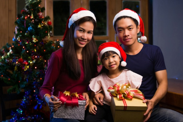 Asian family gift giving and have a merry christmas. at night Premium Photo