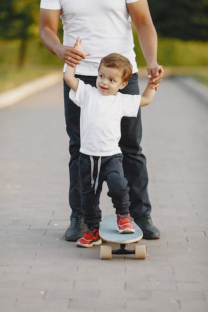 공원에서 아시아 가족. 흰색 T- 셔츠에있는 남자. 아버지는 아들에게 스케이트 타기를 가르칩니다. 무료 사진