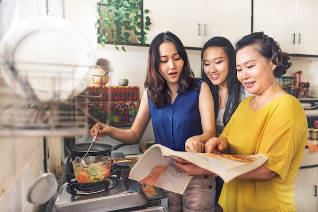 Asian family is cooking in the kitchen together Premium Photo