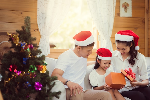 Asian family opening a gift box on christmas day happy Premium Photo