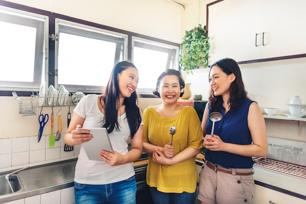 Asian family standing together in the kitchen Free Photo
