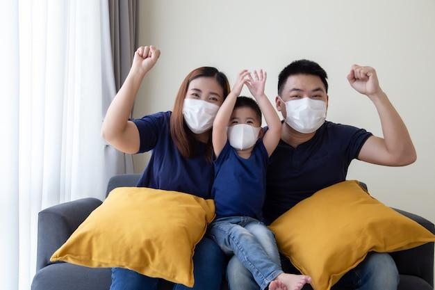 Азиатская семья носить защитную медицинскую маску для предотвращения вируса covid-19 и руки вверх и сидеть вместе в гостиной. защита семьи от концепции загрязненного воздуха Premium Фотографии