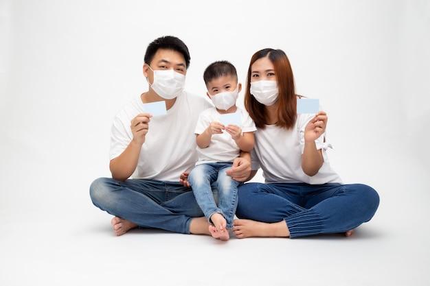 Азиатская семья нося защитную медицинскую маску для предотвращения вируса covid-19 и держа карточку медицинской страховки изолированный на белой стене. концепция защиты семьи и медицинской страховки Premium Фотографии