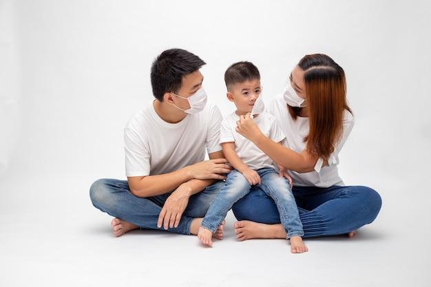 Азиатская семья нося защитную медицинскую маску для предотвращения вируса wuhan covid-19 и сидя совместно на поле изолировала белую стену. защита семьи от концепции загрязненного воздуха Premium Фотографии