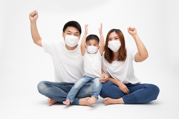 Asian family wearing protective medical mask for prevent virus wuhan covid-19 and hand up and sitting together on floor isolated white wall. family protection from contaminated air concept Premium Photo