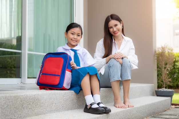 Asian family with mother and daughter sitting and smiling in front of the house to prepare them for kindergarten children who put their school uniform with a backpack go to school in the morning. Premium Photo