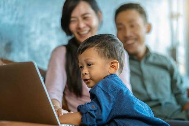 Asian family with son are looking the cartoon via technology laptop and playing together Premium Photo