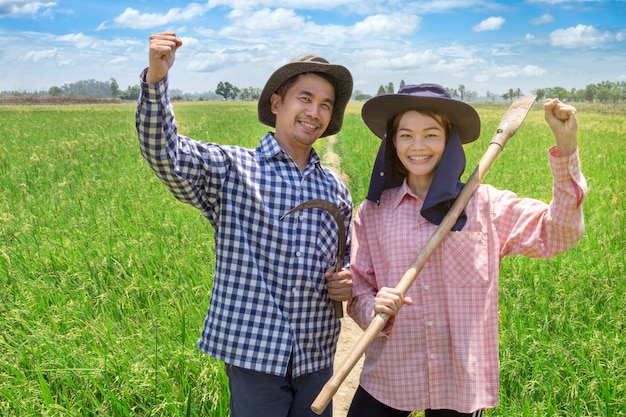 Asian farmers couple holding tools in rice farm at thailand Premium Photo