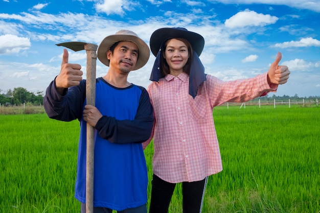 Asian farmers couple holding tools and thumb up in rice farm Premium Photo