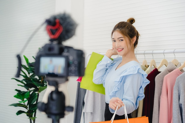 Asian fashion female blogger online influencer holding shopping bags and lots of clothes Free Photo