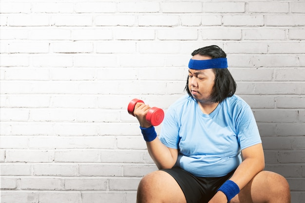 Asian fat man using dumbbell to lose weight Premium Photo