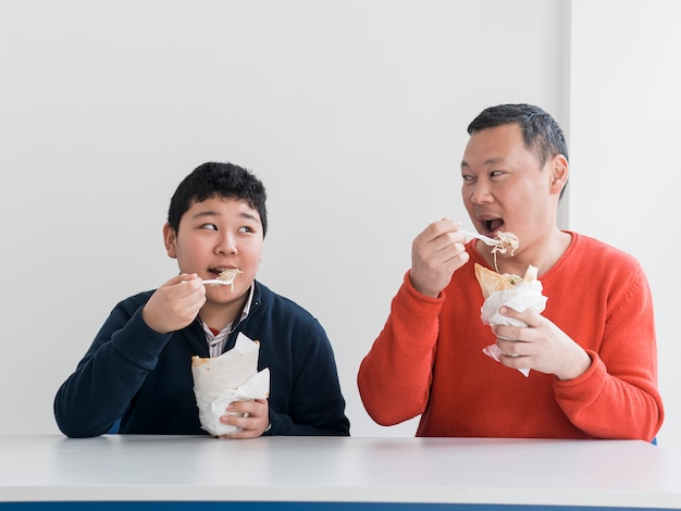 Азиатский отец и сын едят фаст-фуд Бесплатные Фотографии