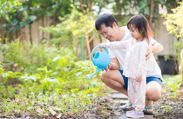Premium Photo | Asian father and daughter are watering vegetables garden at  home.