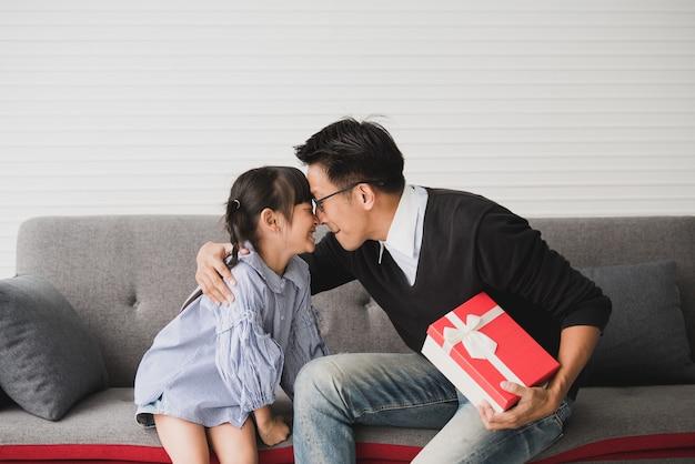 アジアの父親は娘へのプレゼントを差し出しキスをします。誕生日のためのコンセプトサプライズギフトボックス。 Premium写真