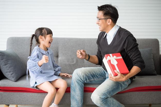 アジアの父親は娘へのプレゼントを差し出します。誕生日のためのコンセプトサプライズギフトボックス。 Premium写真
